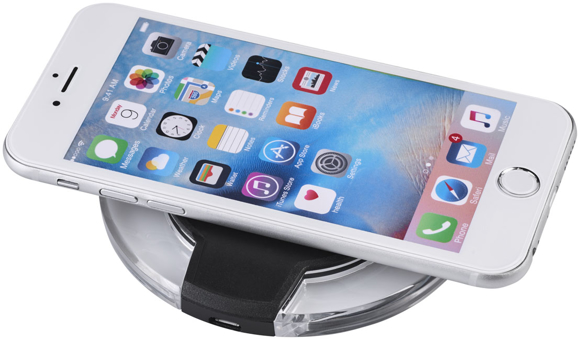 Round wireless charging pad topping up a mobile phones battery