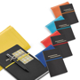 Imitation leather roots notebook in black with grey elastic straps for pens and business cards and coloured elastic closure straps in yellow, dark blue, red, light blue and orange all with colour matching woven pouches