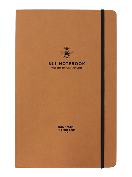Will Bees crown notebook in tan with black elastic closure strap and black embossed logo