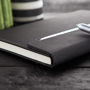 Imitation leather hardcover notebook in black with fold over magnetic lock and stitching detail around edges