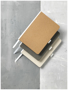medium size cardboard notebooks in brown, charcoal and white with white fabric spine, ribbon and elastic pen loop