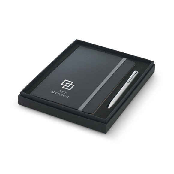 Notepad with hardcover in black with grey elastic closure strap and silver ball point pen in black box