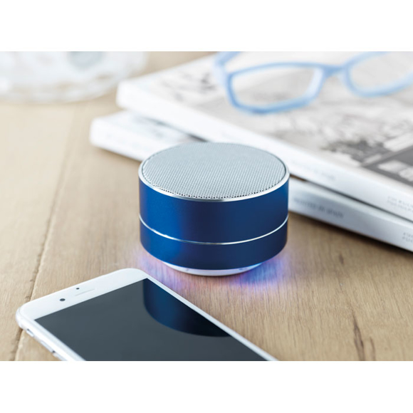 a blue bluetooth speaker next to phone